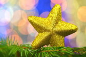 Christmas decoration, golden brocade star against bokeh background — Stockfoto