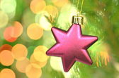 Christmas decoration, pink Christmas star ball hanging on spruce twig against bokeh background — Stock Photo