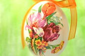 Easter egg decorated with flowers made by decoupage technique on green background — Foto Stock