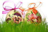 Easter eggs decorated with flowers made by decoupage technique in the grass — Stock Photo