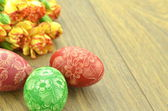 Scratched handmade Easter eggs and carnation flowers — Стоковое фото