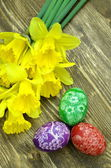 Beautiful scratched handmade Easter eggs and daffodil flowers — Stock Photo