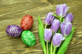Scratched handmade Easter eggs and tulip flowers — Stock Photo
