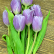 A bouquet of beautiful violet tulips on rustic wooden table — Stock Photo #44776821