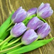 A bouquet of beautiful violet tulips on rustic wooden table — Stock Photo #44776839
