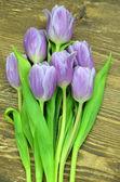 букет красивых фиолетовых тюльпанов на деревенский деревянный столик — Стоковое фото