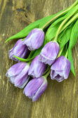 A bouquet of beautiful violet tulips on rustic wooden table — Stock Photo