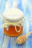 Pote de mel delicioso fresco e dipper mel sobre uma mesa de madeira — Fotografia Stock