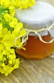 Jar of delicious honey in a jar with rapeseed flowers — Stock Photo