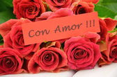 With love wishes in spanish and bouquet of gorgeous red roses — Stock Photo