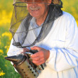 Experienced senior apiarist working in the blooming rapeseed field — Stock Photo #46820757