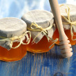 Wooden honey dipper and jars full of delicious fresh honey in apiary — Stock Photo