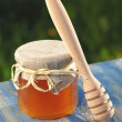 Wooden honey dipper and jar full of delicious fresh honey in apiary — Stock Photo