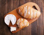 Croissant and cheese on wooden board — Stock Photo