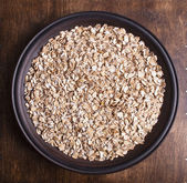Plate with raw oatmeal on wooden table. — Stockfoto