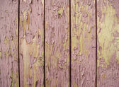 Old wooden planks painted with pink paint cracked by a rustic background — Stock Photo