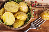 Roasted potato in bowl on wooden table — Zdjęcie stockowe
