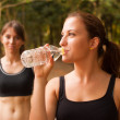 Woman drinking water after sport activities - Stock Photo