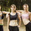 Three attractive women exercising in nature - Stock Photo