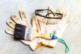 Paint brush and glass on workgloves — Stock Photo