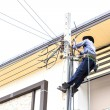 Electrician connects wires on a pole  — Stock Photo