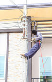 Electrician working on a pole — Stock Photo