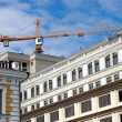 Building crane on the background of city buildings and sky — Foto de Stock