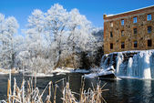 Winter landscape with icy river dam — Stock Photo