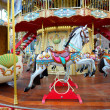 Children carousel running horses — Stock Photo