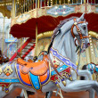Children carousel running horses — Stock Photo #34359875