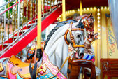 Children carousel running horses — Stock Photo