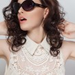 Beautiful young brunette with curly hair in sun glasses. — Stock Photo
