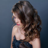 Shy young girl with curly hair — Stock Photo