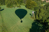 Hot-air balloons shadow on green field with hide — Stock Photo