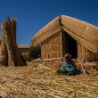 Stock Photo: Womon Uros island sitting in front of her home and working