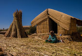 Woman on Uros island sitting in front of her home and working