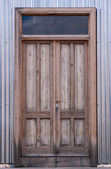 Wooden door in corrugated metal — Stock Photo
