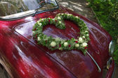 Flower bouquet in heart shape on oldtimer car — Stock Photo
