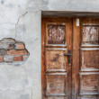 Stock Photo: Run-down wooden entrance door with cracked brick wall