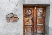 Run-down wooden entrance door with cracked brick wall — Stock Photo