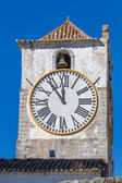 European church with tower and huge clock — Stock Photo
