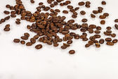 Grain coffee on a white reflective surface with — Stock Photo