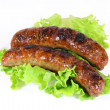 Two tasty grilled sausage with lettuce isolated — Stock Photo #24307111