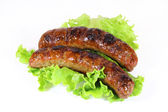 Two tasty grilled sausage with lettuce isolated — Stock Photo
