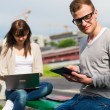 Students with tablet and laptop in park — Stock Photo #42898647