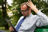 Angry businessman with tablet — Stock Photo