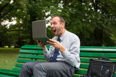 Excited businessman with laptop — Stock Photo