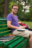 Student with note book on bench — Stock Photo