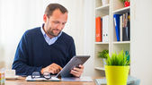 Man with tablet in office — Stock Photo