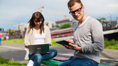 Students with tablet and laptop in park — Stock Photo